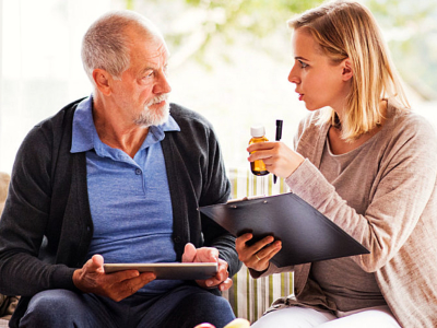caregiver reminding elderly man about his medications
