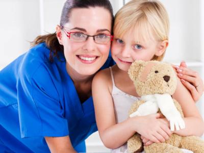 pediatrician hugging young girl holding teddy bear