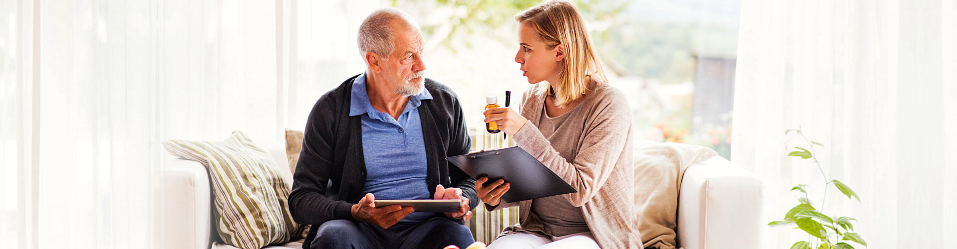 caregiver talking to elderly man about his medications