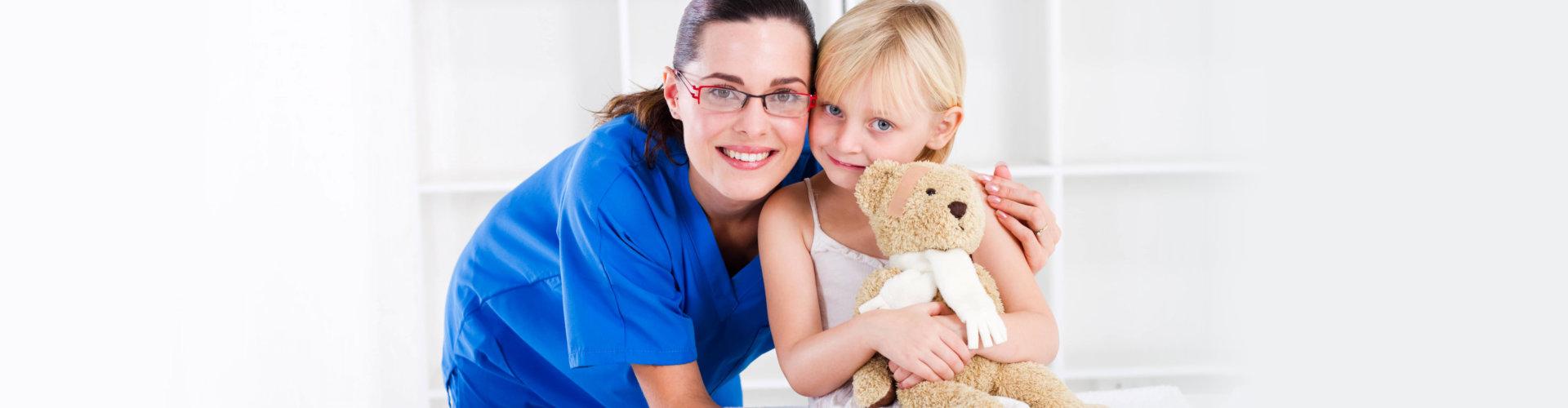 pediatrician hugging young girl holding a bear